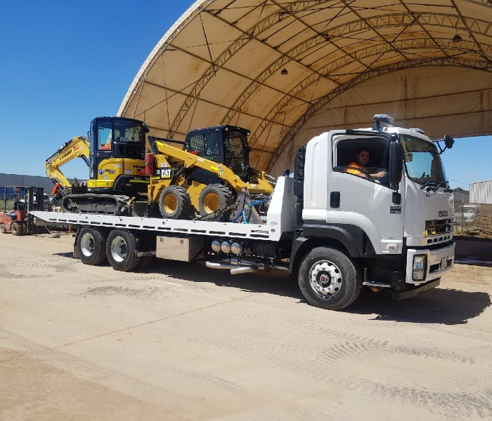 Tow truck towing bob cat and digger