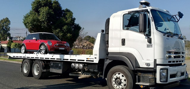 Red Mini car being towed by tow truck