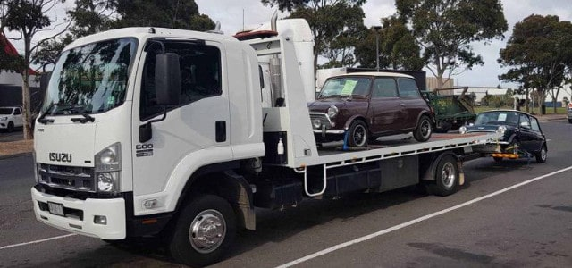Tow truck towing two classic mini cars